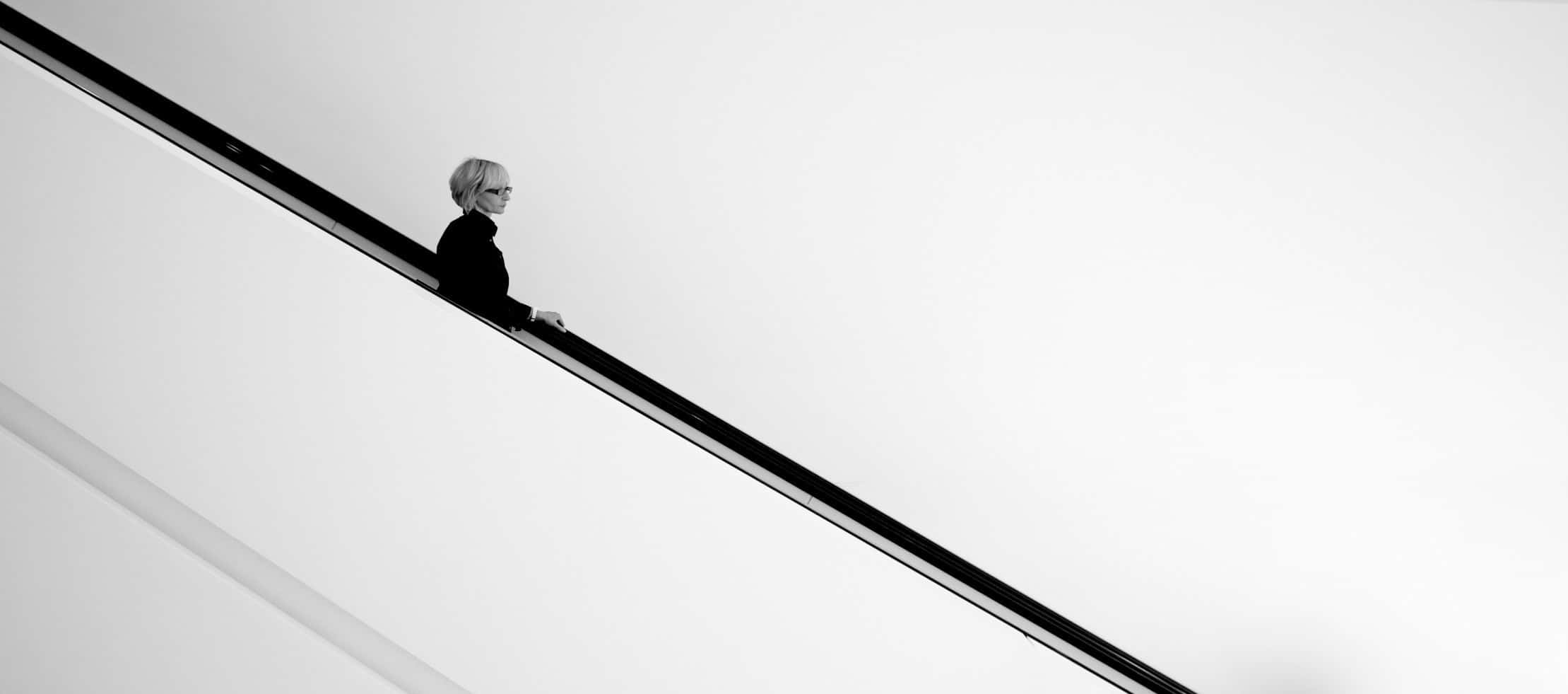Photo of an older woman coming down an escalator, all white negative space around her.