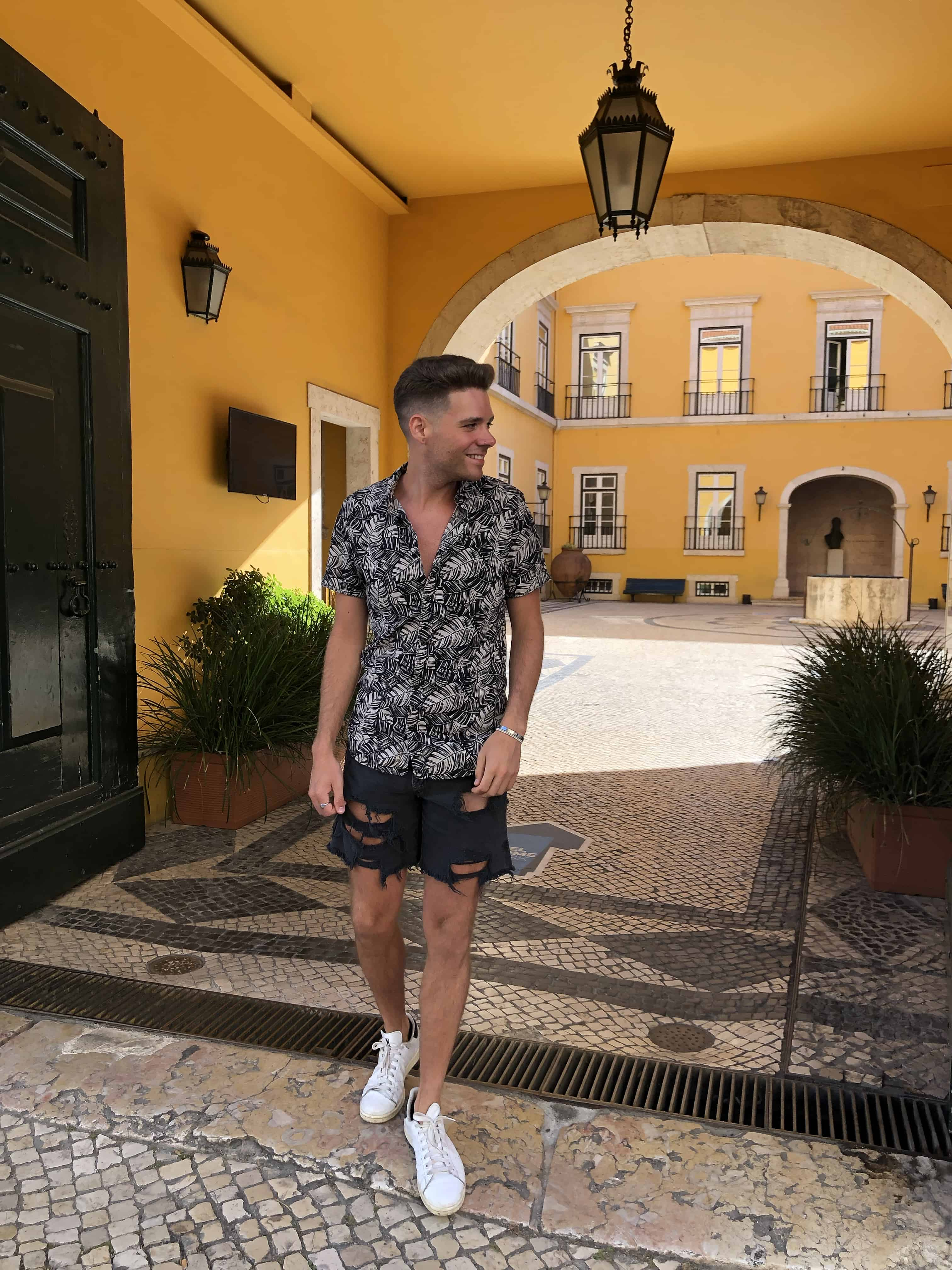 Unedited Image of young man in button down shirt and jean shorts walking in Portugal.