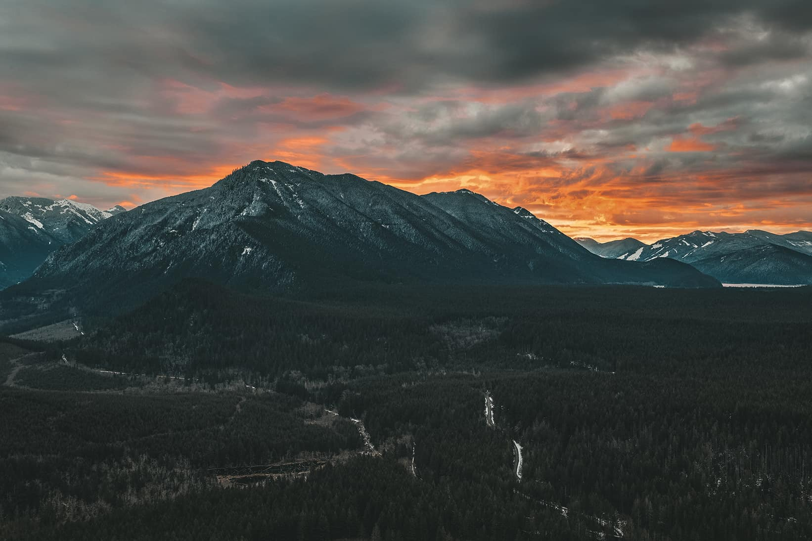 Adobe Lightroom Edited image of a dark mountain with orange fire sunset in the background.