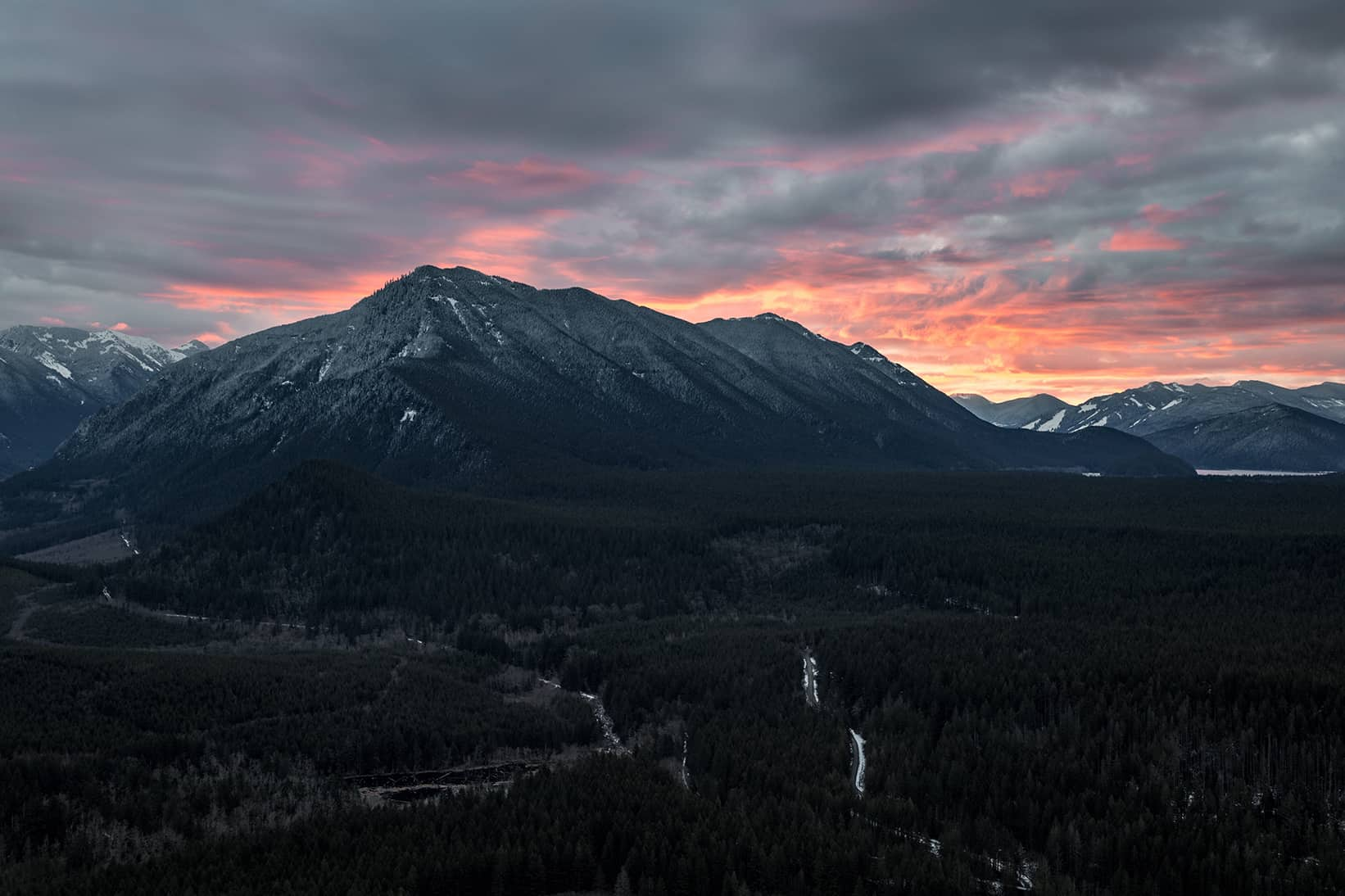 RAW image of a dark mountain with sunset in the background.