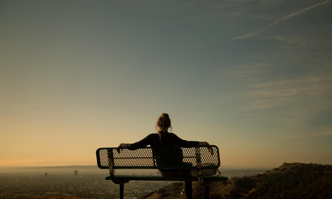 girl sitting being present on bench at sunset