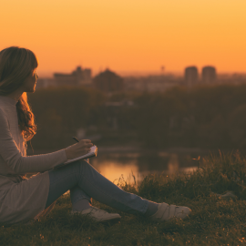 A woman watches a sunset and writes in her notebook