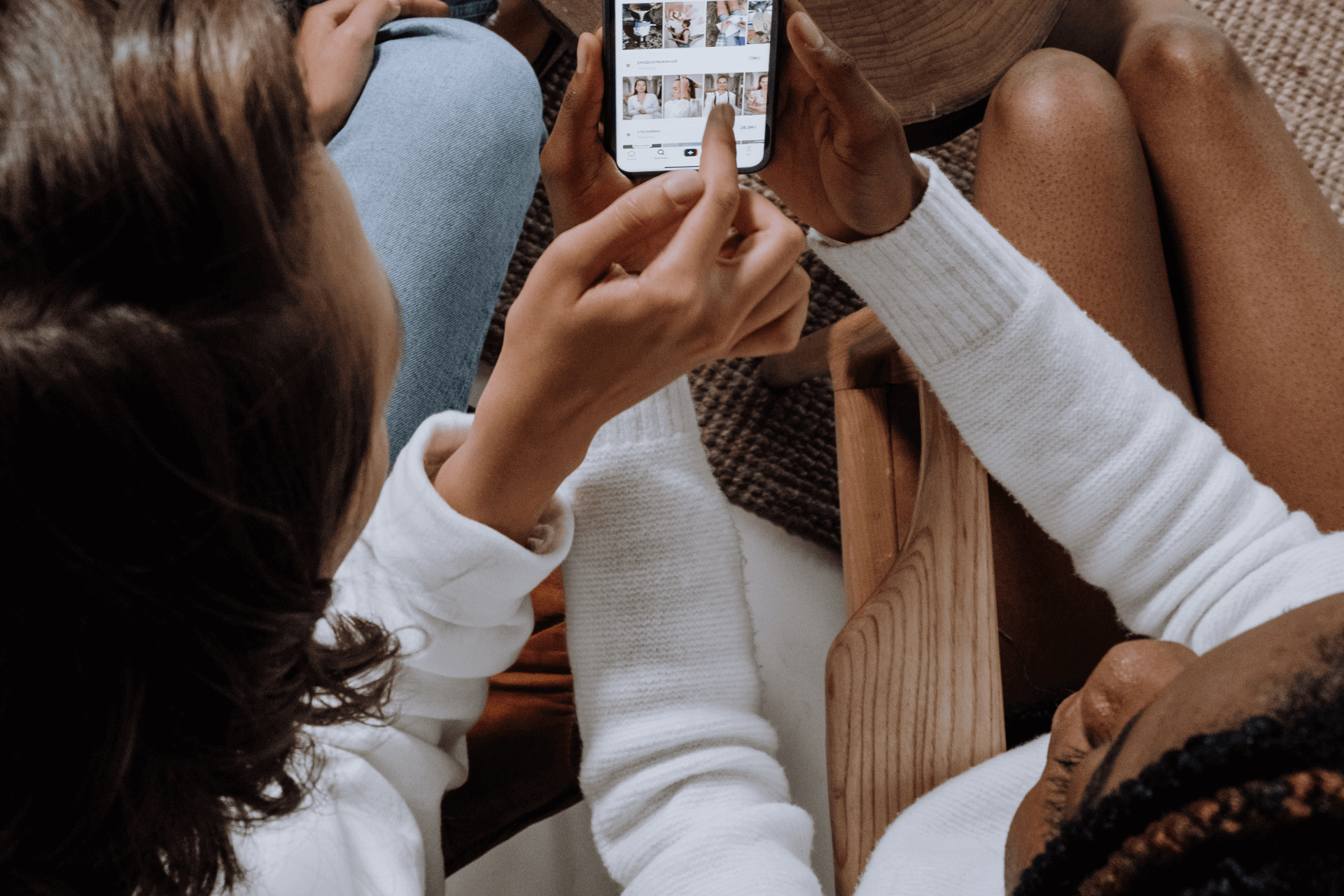 Two women look at TikTok influencers on their phone