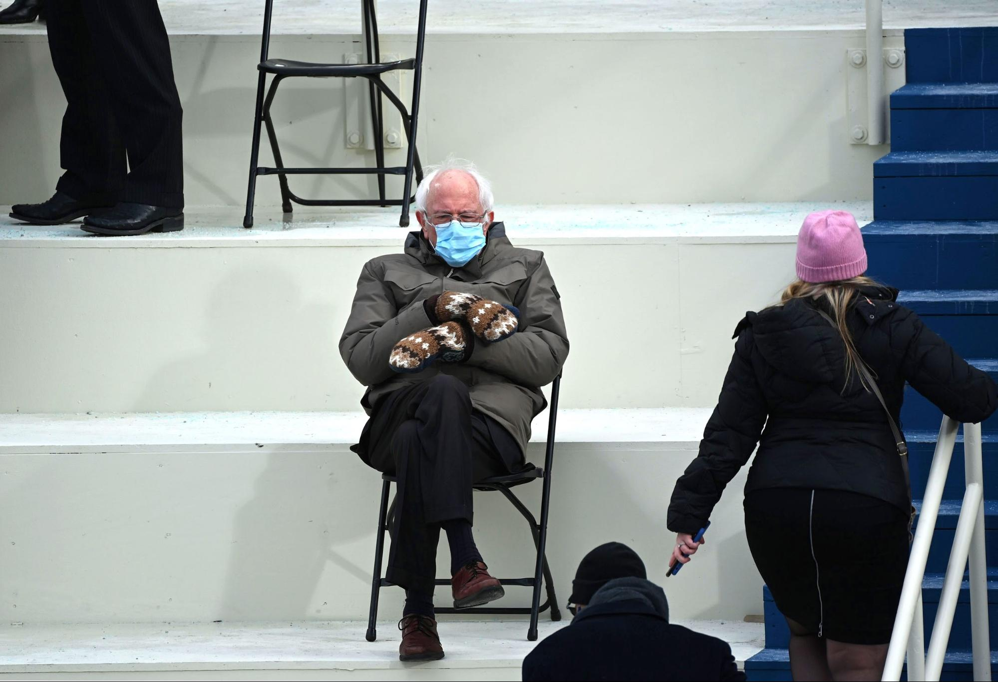 Bernie Sanders sitting with a mask and mittens on