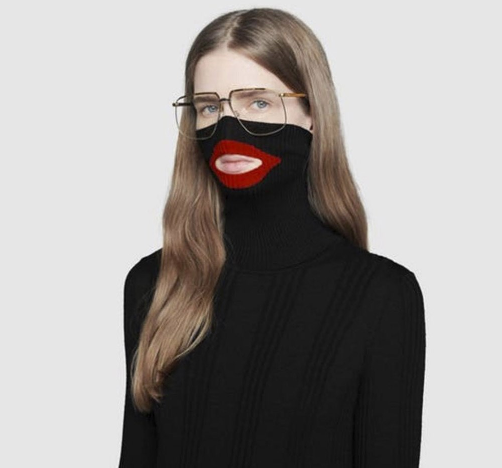 Photo of a white woman with long brown hair and glasses wearing a Black sweater with red lining around the lip area