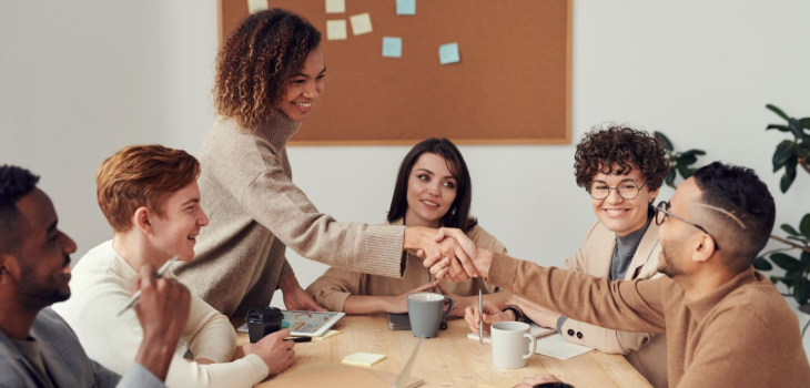 Photo of various genders and races chatting, smiling, and shaking hands in an office environment.