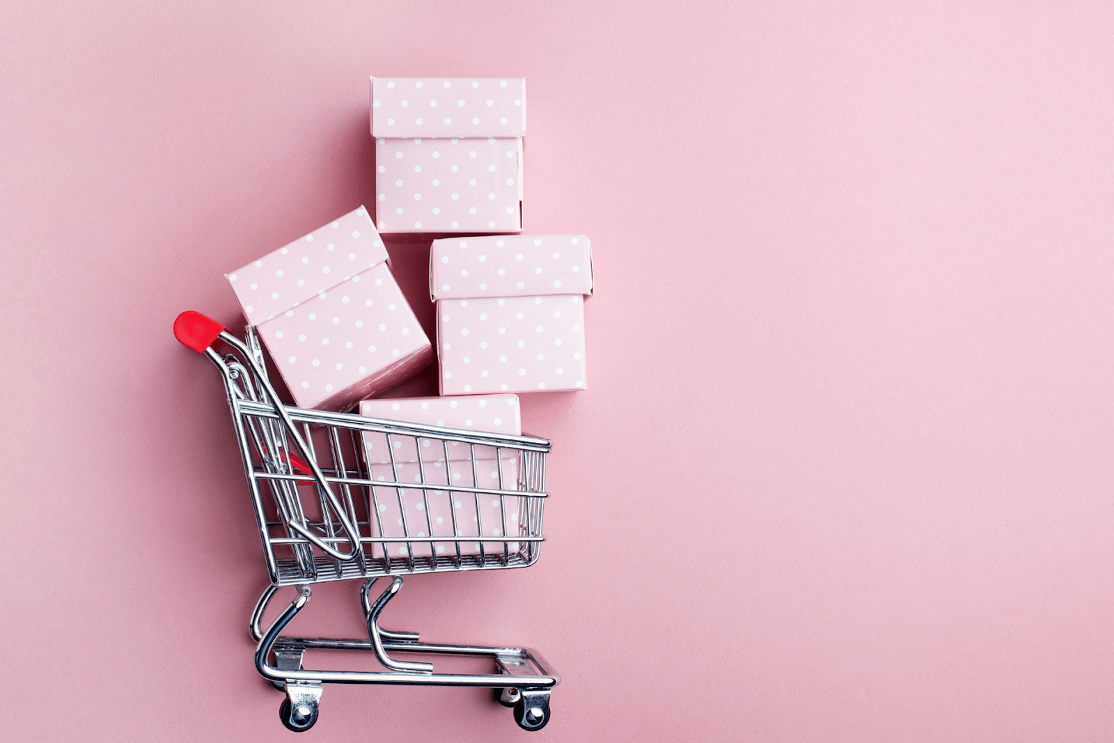 A shopping cart with four pink boxes in it
