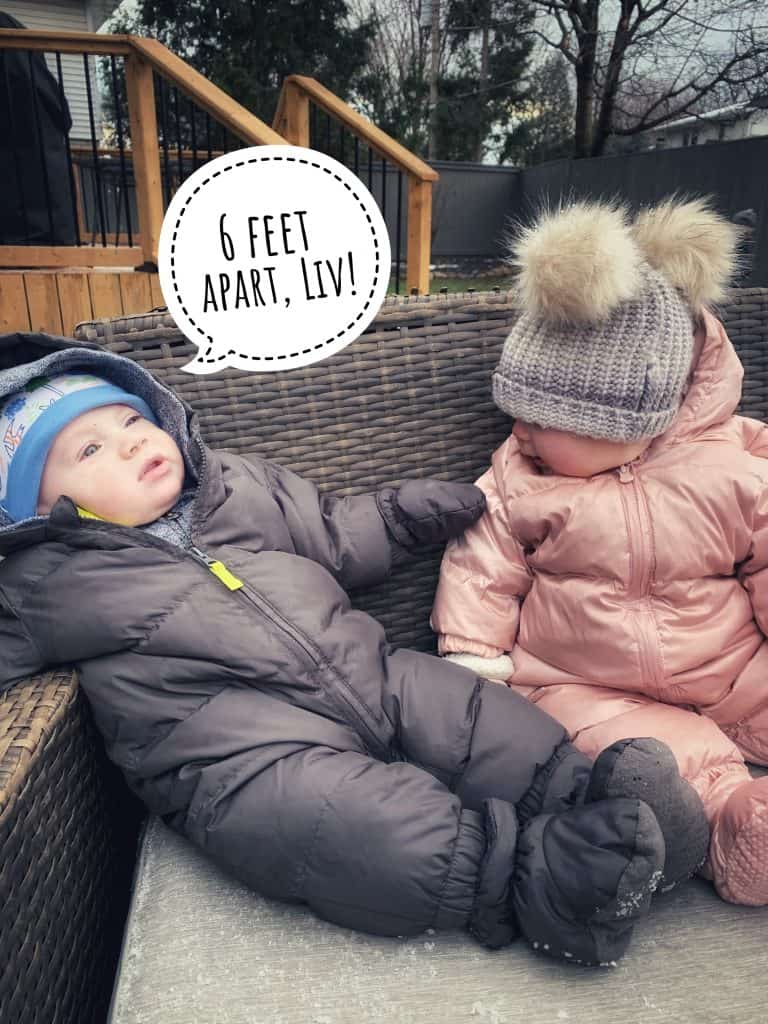 Two babies sitting on a chair outdoors