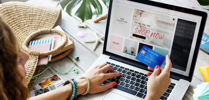 A woman holding a credit card, making an online purchase on a laptop