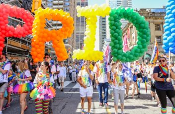 A photo from Toronto Pride, feature a large crowd walking down Yonge Street in Toronto, and 5 people holding large coloured balloon letters that spell PRIDE.