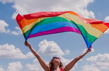 A person waving a Pride flag in the air