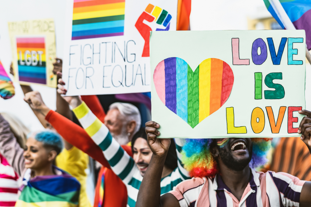 A group of Pride activists holding signs at an event for LGBTQ+ rights