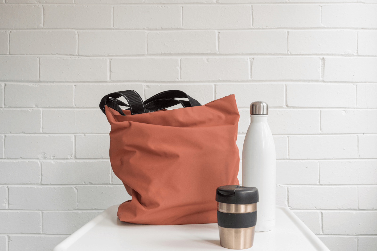 A reusable bag, water bottle, and mug at an office